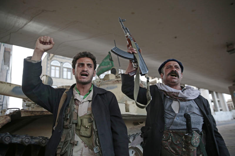 FILE - In this Dec. 4, 2017, file photo, Houthi Shiite fighters chant slogans as they guard a street leading to the residence of former Yemeni President Ali Abdullah Saleh, in Sanaa, Yemen. A senior leader from Yemen's Houthi rebels says that for the sake of peace efforts the group will halt rocket fire into Saudi Arabia, its larger northern neighbor who is leading a U.S.-backed Arab coalition to restore Yemen's internationally recognized government. (AP Photo/Hani Mohammed, File)