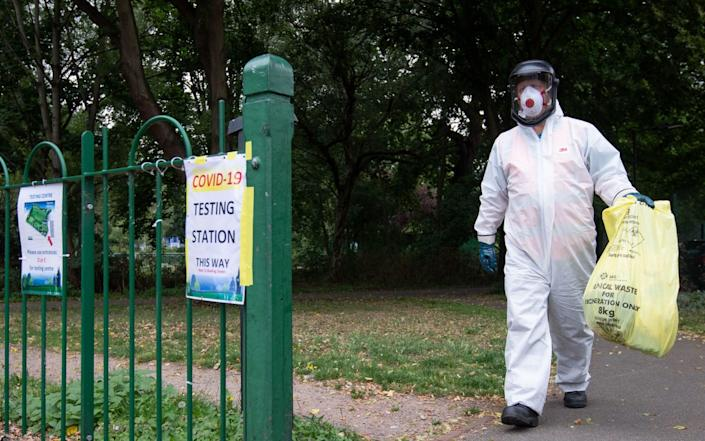 A worker for Leicester City Council carries a bag of clinical waste away from a Covid-19 testing station at Spinney Hill Park in Leicester where Leicester local coronavirus lockdown restrictions have been in place since June 29, with non-essential shops ordered to close and people urged not to travel in or out of the area. - Joe Giddens/PA