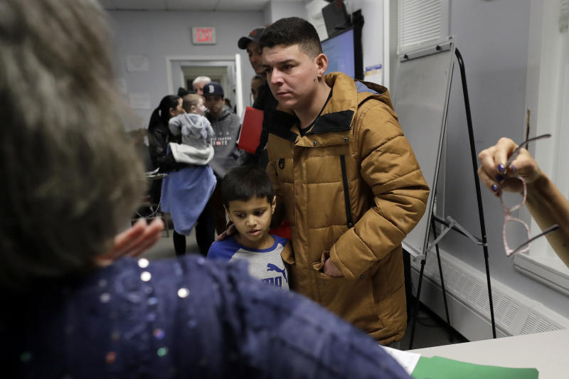 In this Wednesday, Dec. 4, 2019 photo Helison Alvarenga, of Brazil, center right, and his 6-year-old son, David, center left, move away from a reception table after speaking with volunteers at the New England Community Center, in Stoughton, Mass. Alvarenga, a 26-year-old from the Brazilian state of Minas Gerais, arrived in Massachusetts about four months ago after crossing the Mexican border at Juarez with his 24-year-old wife, Amanda, and his son David. The family were at the community center Dec. 4 to apply for new Brazilian passports, which Alvarenga says were seized by border officials. (AP Photo/Steven Senne)