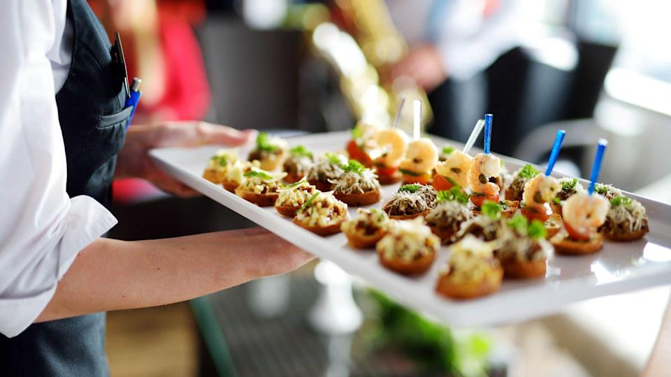 Waiter carrying plates with meat dish on some festive event, party or wedding reception.
