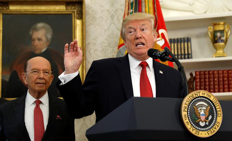 Commerce Secretary Wilbur Ross stands behind President Donald Trump, who speaks at the Minority Enterprise Development Week White House awards ceremony on Oct. 24. (Kevin Lamarque / Reuters)