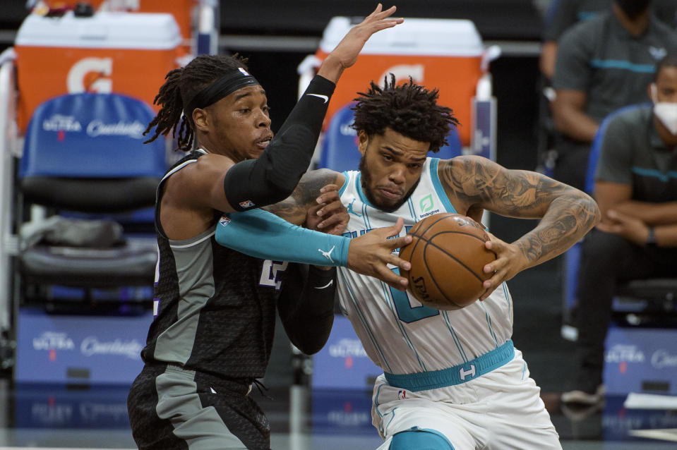 Sacramento Kings guard Buddy Hield (24) defends against Charlotte Hornets forward Miles Bridges (0) during the first quarter of an NBA basketball game in Sacramento, Calif., Sunday, Feb. 28, 2021. (AP Photo/Randall Benton)