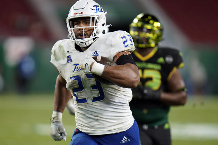 FILE - Tulsa linebacker Zaven Collins (23) runs back an interception for a score against South Florida during the second half of an NCAA college football game in Tampa, Fla., in this Friday, Oct. 23, 2020, file photo. Zaven Collins is a small-town player with big-time talent. He was overlooked after a stellar high school career in Hominy, Okla., a town with about 3,500 people. He's got the nation's attention now -- the 6-foot-4, 260-pound linebacker is a finalist for the Butkus and Nagurski Awards. (AP Photo/Chris O'Meara, File)