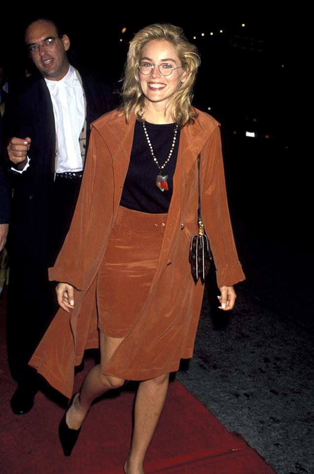 <p>Sharon Stone tops off a matching burnt orange two-piece with a rare pair of round glasses at the Los Angeles premiere of <em>Air America</em> in August 1990.</p>
