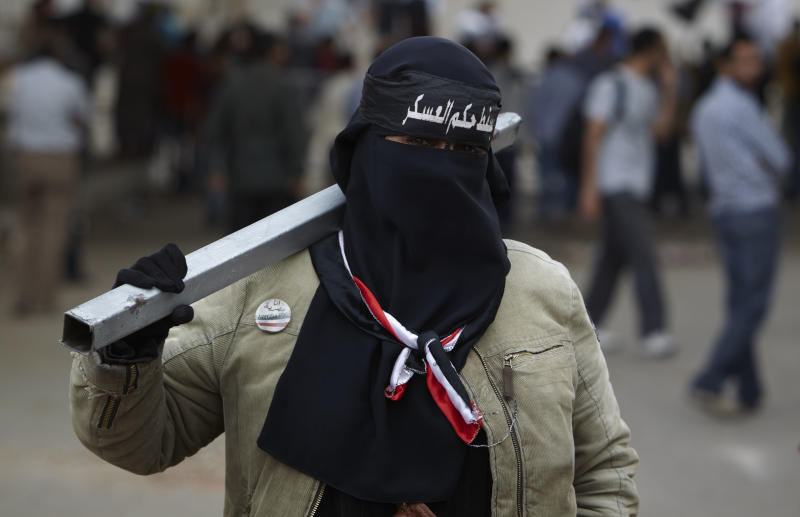 """In this Monday, April 30, 2012 photo, an Egyptian women wearing the Niqab with Arabic writing that reads, """"down with military rule,"""" carries a metal pole as a weapon at the road leading to the Ministry of Defense, in Cairo, Egypt. (AP Photo/Fredrik Persson)"""