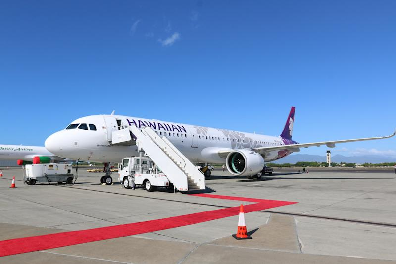 A Hawaiian Airlines A321neo jet parked on the tarmac, with air stairs attached