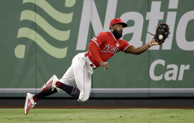 Los Angeles Angels center fielder Brian Goodwin dives to make a catch on a line drive by Oakland Athletics' Chad Pinder during the sixth inning of a baseball game Wednesday, Sept. 25, 2019, in Anaheim, Calif. (AP Photo/Marcio Jose Sanchez)