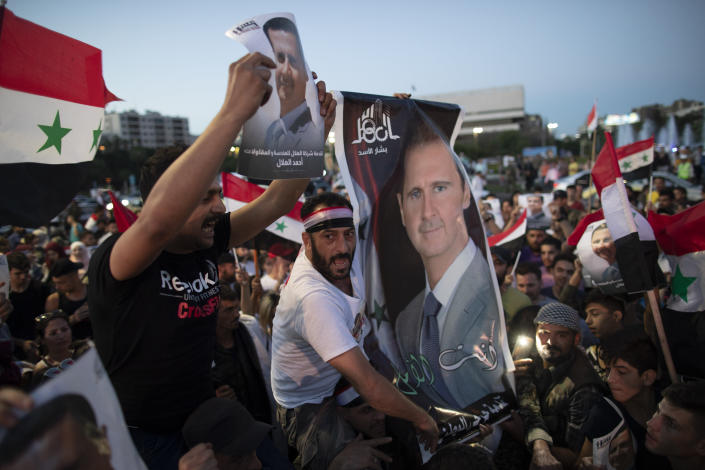 Injured Syrian soldiers supporters of President Bashar Assad hold up national flags and pictures of Assad as they celebrate at Omayyad Square, in Damascus, Syria, Thursday, May 27, 2021. (AP Photo/Hassan Ammar)