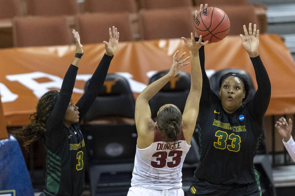 Wright State guard Jada Roberson (3) and center Tyler Frierson (33) defend Arkansas guard Chelsea Dungee (33) during the first half of a college basketball game in the first round of the women's NCAA tournament at the Frank Erwin Center in Austin, Texas, Monday, March 22, 2021. (AP Photo/Stephen Spillman)