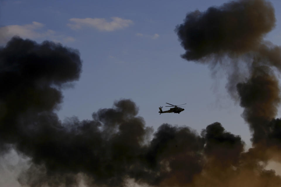 An Israeli Air Force Apache attack helicopter flies during a graduation ceremony for new pilots in the Hatzerim air force base near the city of Beersheba, Israel, Wednesday, Dec. 26, 2018. (AP Photo/Ariel Schalit)