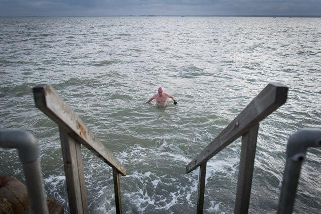 Swimmers take their daily dip in the Thames estuary at Leigh-on Sea in Essex