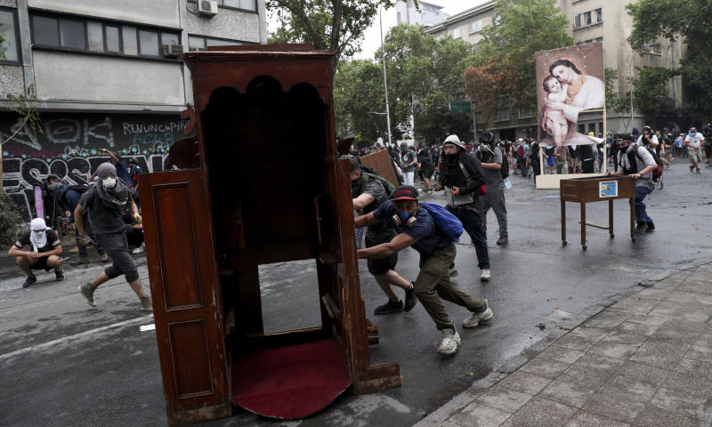 Anti-government protesters drag items from a church to be added to a barricade, in Santiago, Chile, Friday, Nov. 8, 2019.  Chile's president on Thursday announced measures to increase security and toughen sanctions for vandalism following three weeks of protests that have left at least 20 dead. (AP Photo/Esteban Felix)