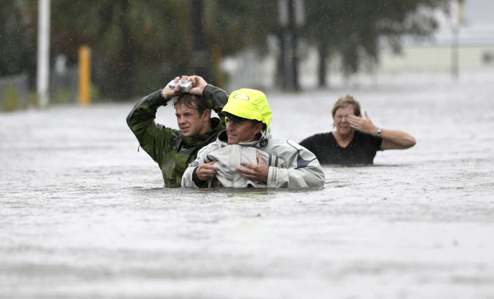 Chuck Cropp, center, his son Piers, left, and wife Liz, right, wade through floodwaters from Hurricane Isaac Wednesday, Aug. 29, 2012, in New Orleans. As Isaac made landfall, it was expected to dump as much as 20 inches of rain in several parts of Louisiana. (AP Photo/David J. Phillip)