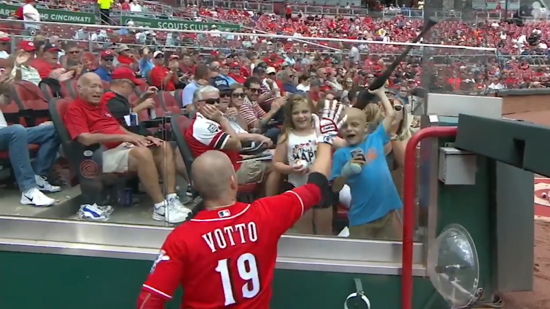 "Joey Votto handing his bat to 6-year-old cancer patient Walter ""SuperBubz"" Herbert. (MLB.com)"