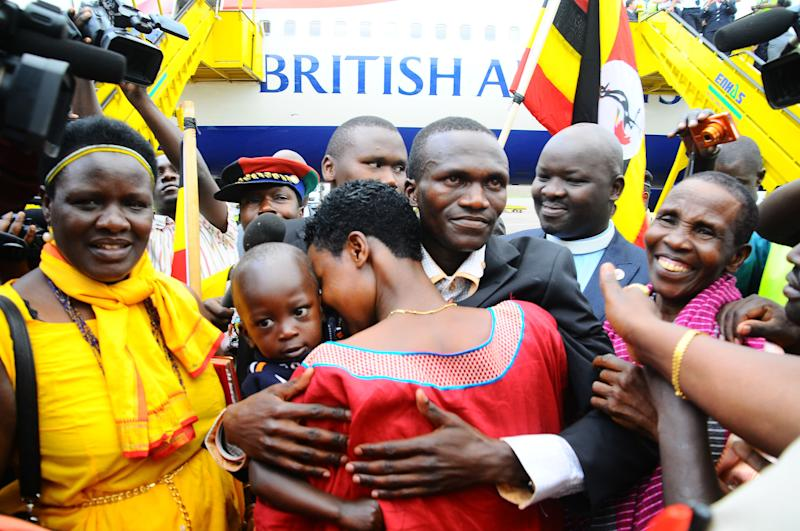 Ugandan Olympic Gold medaliist marathon champion Stephen Kiprotich, centre in suit, being received by his wife and relatives at Entebbe International Airport 42kms from the capital Kampala, Uganda, Wednesday Aug. 15, 2012 Kiprotich's win has been deeply felt in Uganda, which had not won gold since the Munich Games in 1972. Lawmakers are considering a motion that declares Kiprotich a national hero, his employer has promised to promote him at work. (AP Photo/ Stephen Wandera)