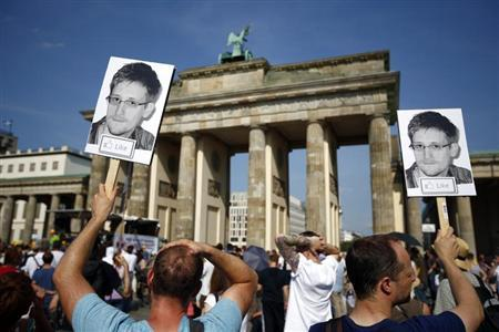 Protesters carry portraits of Snowden during a demonstration against secret monitoring programmes PRISM, TEMPORA, INDECT and showing solidarity with whistleblowers Snowden, Manning and others in Berlin
