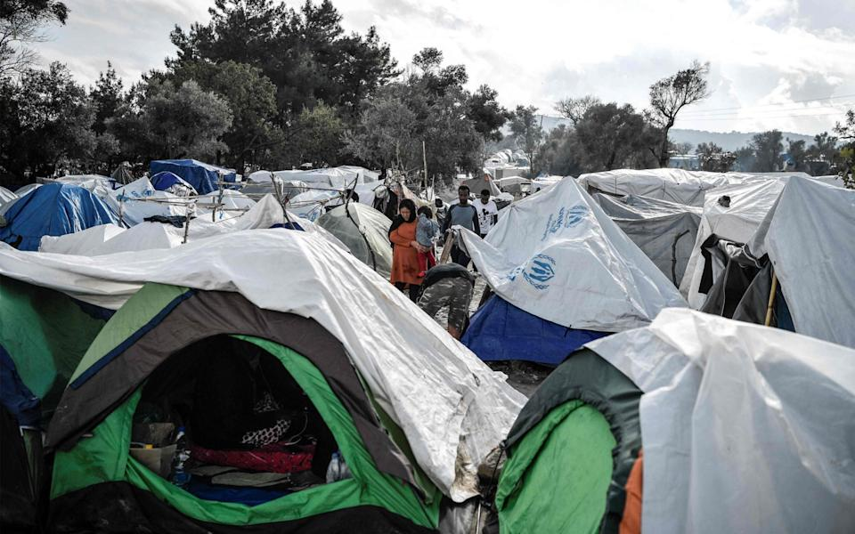 People walking among the tents in the Vial refugee camp, on the Greek island of Chios, in December 2019. This island has reported its first Covid-19 infection today in one of its overcrowded asylum seeker camps - LOUISA GOULIAMAKI/AFP via Getty