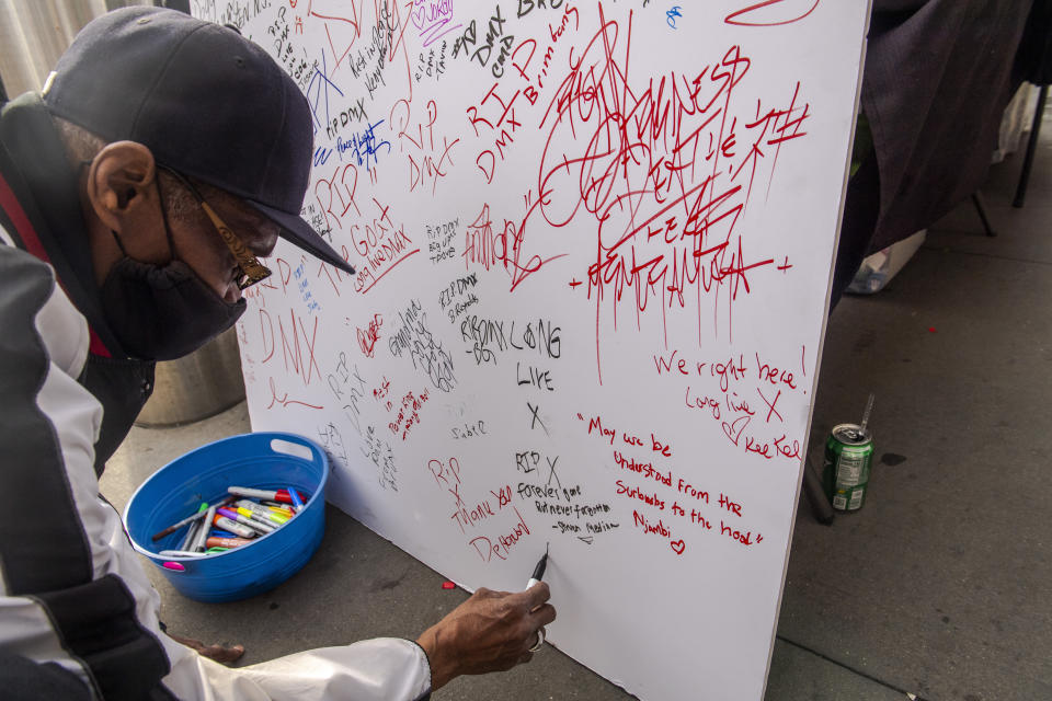 "Ivey Bronson, 59, writes a note on a board for a ""Celebration of Life Memorial"" for rapper DMX at Barclays Center, Saturday, April. 24, 2021, in the Brooklyn borough of New York. DMX, whose birth name is Earl Simmons, died April 9 after suffering a ""catastrophic cardiac arrest."" (AP Photo/Brittainy Newman)"
