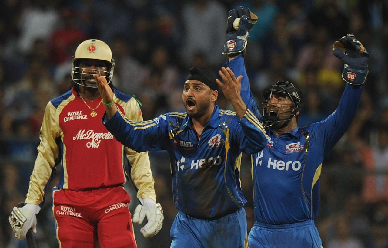 Mumbai Indians cricketers Harbhajan Singh (C) and Dinesh Karthik appeal unsuccessfully against Royal Challengers Bangalore batsman Chris Gayle (L) during the IPL Twenty20 cricket match between Mumbai Indians and Royal Challengers Bangalore at The Wankhede Stadium in Mumbai on May 9, 2012.  RESTRICTED TO EDITORIAL USE. MOBILE USE WITHIN NEWS PACKAGE    AFP PHOTO/Indranil MUKHERJEE        (Photo credit should read INDRANIL MUKHERJEE/AFP/GettyImages)