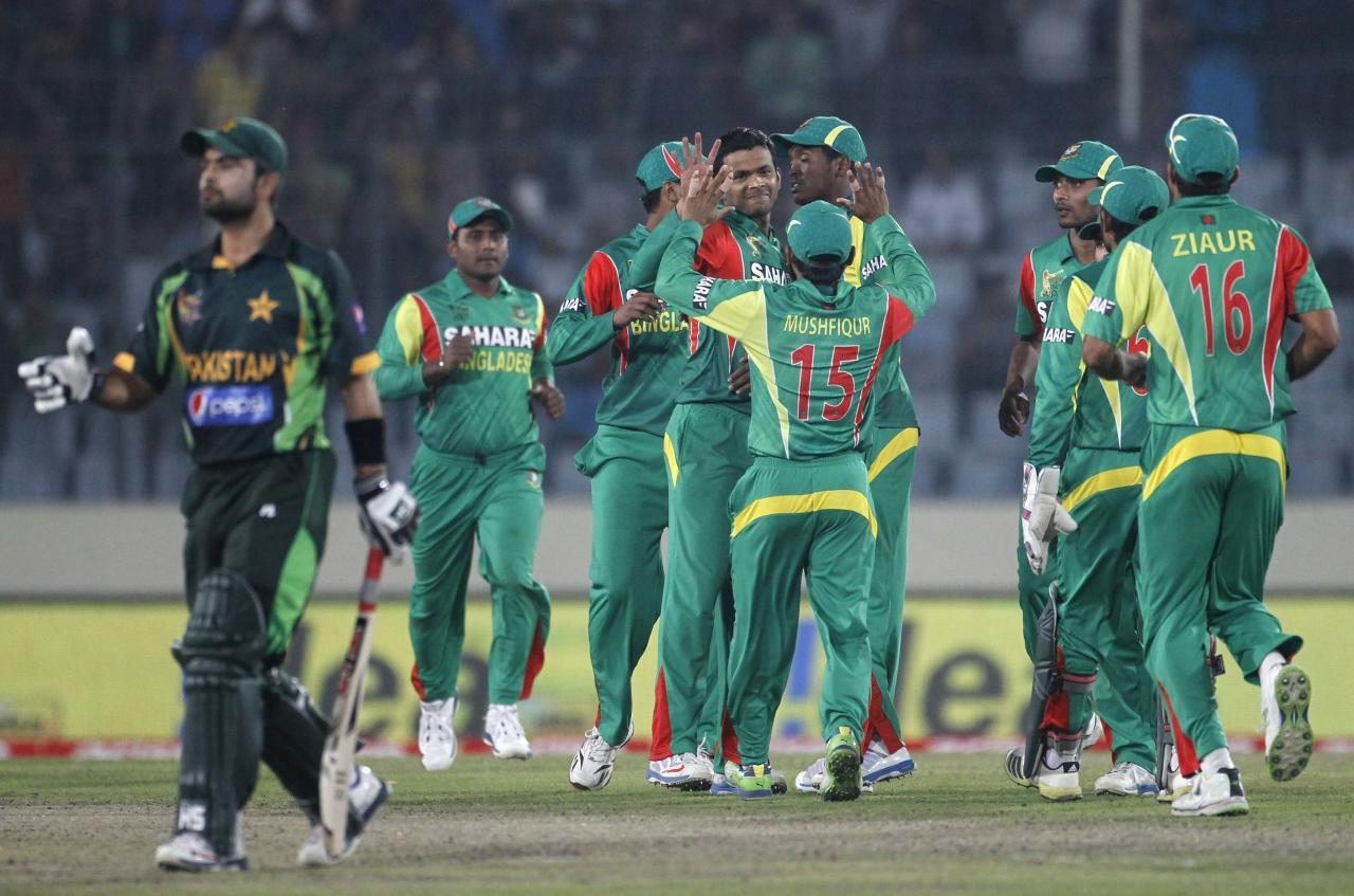 Pakistan's Ahmed Shehzad (L) leaves the field as Bangladesh's fielders celebrate his dismissal during their one-day international (ODI) cricket match in Asia Cup 2014 in Dhaka March 4, 2014. REUTERS/Andrew Biraj (BANGLADESH - Tags: SPORT CRICKET)