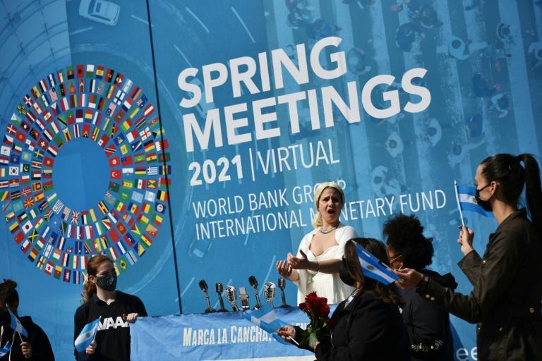 An activist dressed as Argentina's Evita Peron takes part in a Washington rally calling for debt relief during the virtual spring meetings of the World Bank and International Monetary Fund on April 8, 2021