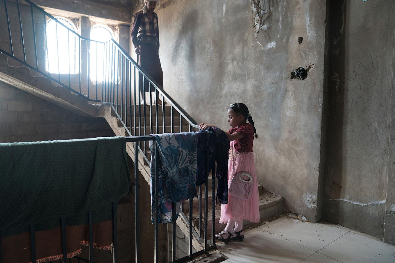 <p>Al Abthi building, Ibb City, Yemen, April 21, 2017: A young girl and her father on the stairs of a former government building in the suburbs of Ibb. The building was provided by local authorities to house 53 displaced families who fled here from Taizz after heavy fighting flared up in the summer of 2015. The building has no electricity or running water. The displaced families installed solar panels on the roof of the building to provide power for rudimentary lighting at night. Many of the children help their parents by collecting water and tending to the younger children in the building. (Photograph by Giles Clarke for UN OCHA/Getty Images) </p>