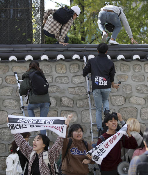 """In this Friday, Oct. 18, 2019, photo, college students use ladders to climb walls of the U.S. ambassador's residence in Seoul, South Korea. South Korean police have formally on Monday, Oct. 21. arrested four anti-American students who broke into the U.S. ambassador's residence in Seoul while protesting the Trump administration's demands for South Korea to pay more to help cover the costs of keeping U.S. troops. The sign reads """"Harris, leave this land!"""" (Kim Sun-ung/Newsis via AP)"""