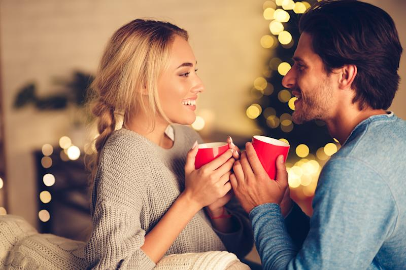 Couple in love drinking tea and enjoying winter holidays in front of Christmas tree