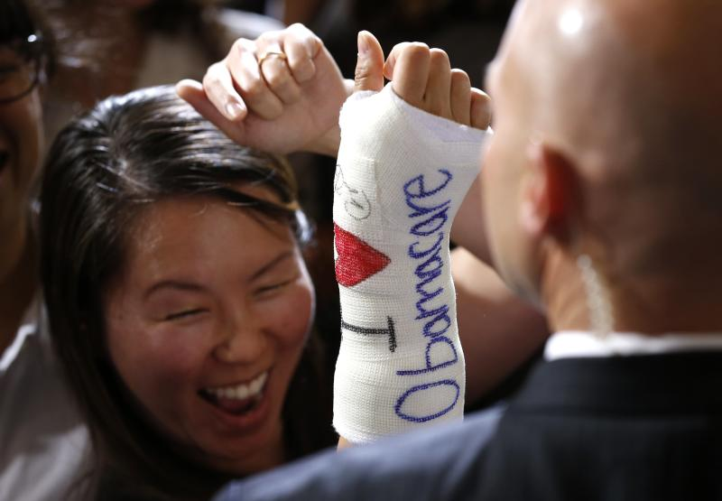 """Cathey Park of Cambridge, Massachusetts reacts after U.S. President Barack Obama signed her cast during a health insurance event at Faneuil Hall in Boston October 30, 2013. The cast reads, """"I Love Obamacare."""" REUTERS/Kevin Lamarque (UNITED STATES - Tags: POLITICS HEALTH)"""