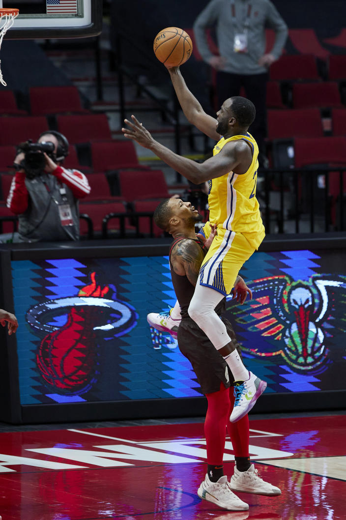 Portland Trail Blazers guard Damian Lillard, left, takes a charge from Golden State Warriors forward Draymond Green in the final seconds of the second half of an NBA basketball game in Portland, Ore., Wednesday, March 3, 2021. (AP Photo/Craig Mitchelldyer)