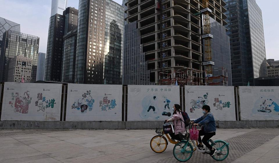 Two women ride past a construction site in the central business district of Beijing on Friday. Photo: AFP