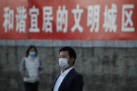 "People wearing face masks to help curb the spread of the coronavirus walk by a banner which reads ""Harmonious and livable civilized city"" on display along a street in Beijing, Tuesday, Oct. 27, 2020. (AP Photo/Andy Wong)"