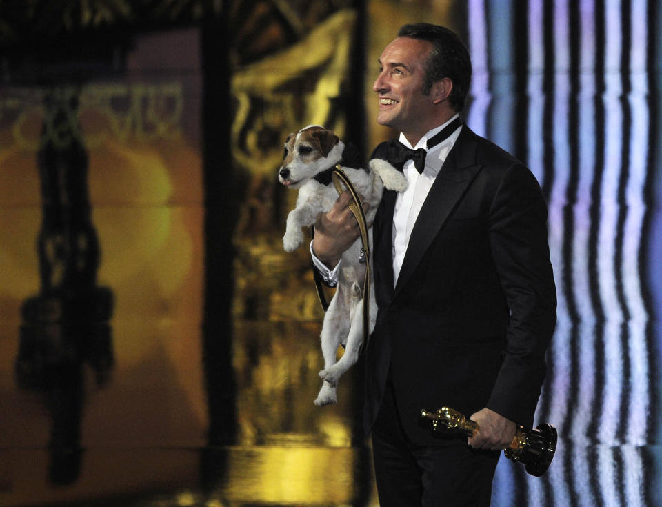 """Jean Dujardin holds Uggie after accepting the Oscar for best picture for """"The Artist"""" during the 84th Academy Awards on Monday, Feb. 27, 2012. (AP Photo/Mark J. Terrill)"""
