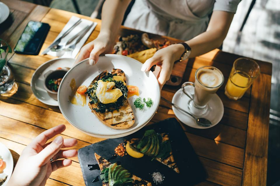 High angle view of woman passing platter of food to friend during brunch in an outdoor restaurant against beautiful sunlight