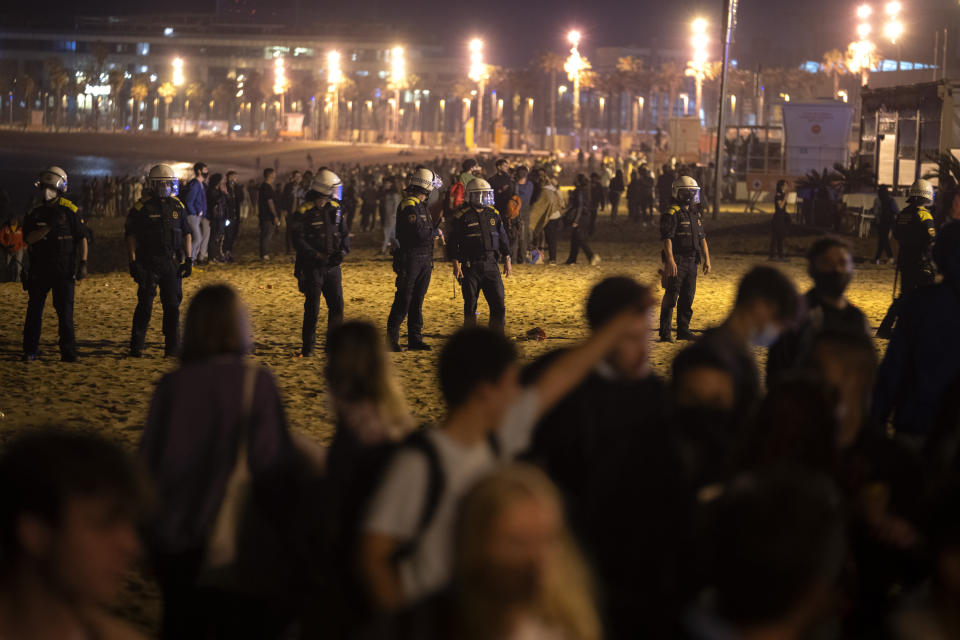 Police officers stand guard as people crowded on the beach in Barcelona, Spain, Sunday, May 9, 2021. Barcelona residents were euphoric as the clock stroke midnight, ending a six-month-long national state of emergency and consequently, the local curfew. Spain is relaxing overall measures to contain the coronavirus this weekend, allowing residents to travel across regions, but some regional chiefs are complaining that a patchwork of approaches will replace the six-month-long national state of emergency that ends at midnight on Saturday. (AP Photo/Emilio Morenatti)