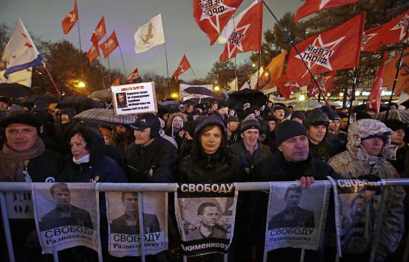 Demonstrators hold posters with portraits of jailed opposition activists Vladimir Akimenkov and Leonid Razvozzhayev and demanding their release, during a protest rally  in Moscow, Russia, Tuesday, Oct. 30, 2012. Several hundred people rallied in central Moscow Tuesday in support of jailed opposition activists. The rally, which was sanctioned by authorities, went on peacefully amid heavy police cordons. It attracted supporters of both leftist and liberal parties, who urged the government to release more than a dozen of people facing accusations over their involvement in an opposition protest in May that ended in clashes with police. (AP Photo/Mikhail Metzel)