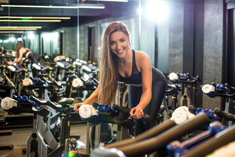 Fit young woman riding cycling indoor bike in gym.