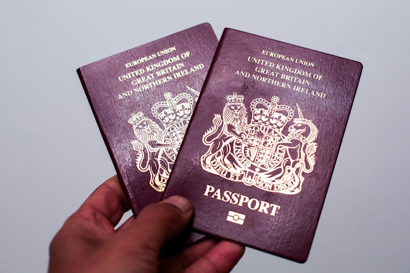 "LONDON, UNITED KINGDOM - 2019/11/20: In this photo illustration a man holds 2 British passports in London. According to the Liberal Democrats manifesto, if they win the general election on 12 December 2019, British passports will feature an ""X"" option for people who identify as gender-neutral. (Photo Illustration by Dinendra Haria/SOPA Images/LightRocket via Getty Images)"