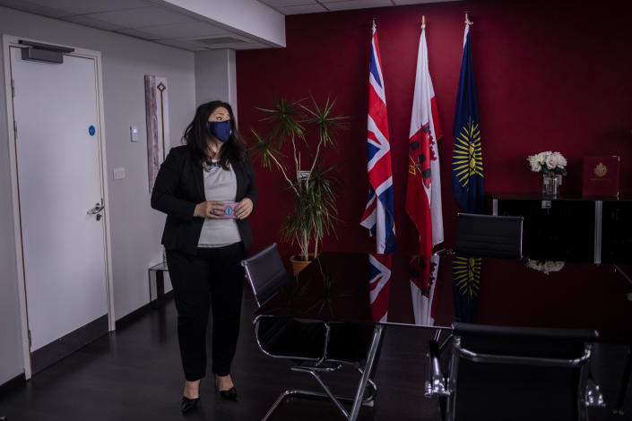 """Gibraltar Health Minister Samantha Sacramento at her office prior to an interview with The Associated Press, in Gibraltar, Thursday, March 4, 2021. Gibraltar, a densely populated narrow peninsula at the mouth of the Mediterranean Sea, is emerging from a two-month lockdown with the help of a successful vaccination rollout. The British overseas territory is currently on track to complete by the end of March the vaccination of both its residents over age 16 and its vast imported workforce. But the recent easing of restrictions, in what authorities have christened """"Operation Freedom,"""" leaves Gibraltar with the challenge of reopening to a globalized world with unequal access to coronavirus jabs.(AP Photo/Bernat Armangue)"""