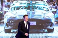 Tesla Inc CEO Elon Musk walks next to a screen showing an image of Tesla Model 3 car during an opening ceremony for Tesla China-made Model Y program in Shanghai