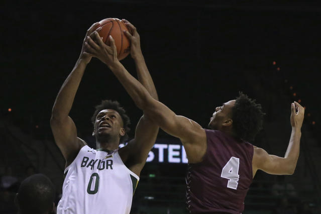 Baylor forward Flo Thamba, left, pulls down a rebound over Maryland-Eastern Shore guard Kevon Voyles, right, in the second half of an NCAA college basketball game, Tuesday, Dec. 3, 2019, in Waco, Texas. Baylor won 78-46. (AP Photo/Rod Aydelotte)