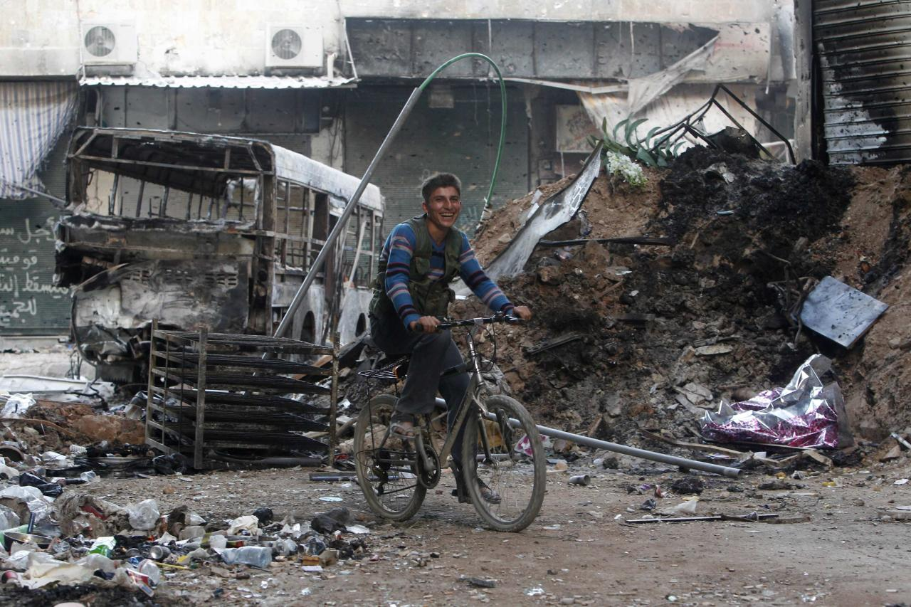 A Free Syrian Army fighter smiles as he rides a bicycle in Ashrafieh, Aleppo September 20, 2013. REUTERS/Muzaffar Salman (SYRIA - Tags: POLITICS CIVIL UNREST CONFLICT TPX IMAGES OF THE DAY)