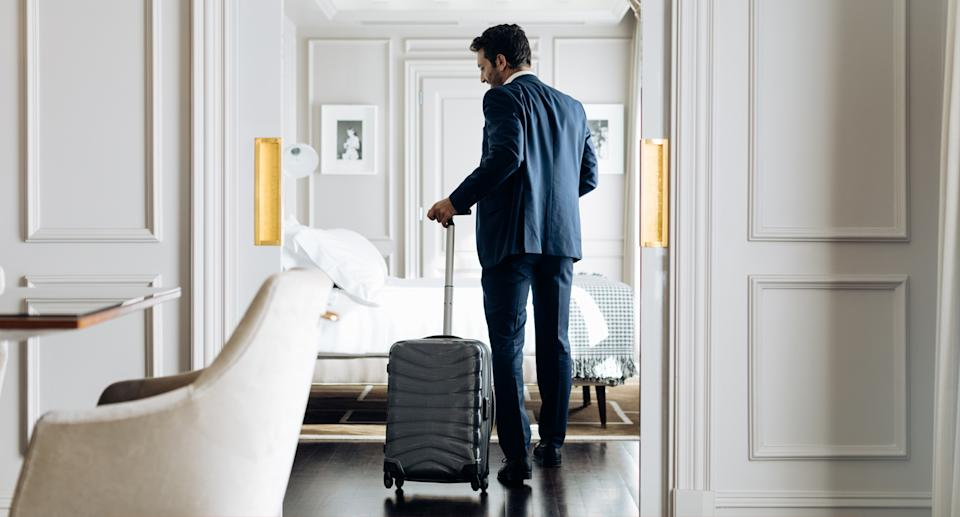 A man walking into a hotel room