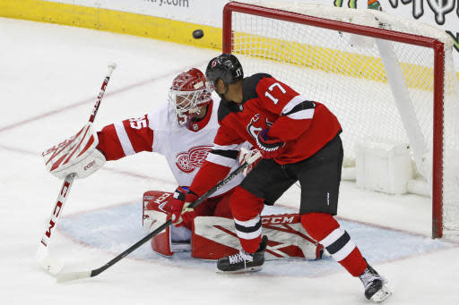 The puck skips over Detroit Red Wings goaltender Jonathan Bernier (45) on a shot by New Jersey Devils right wing Wayne Simmonds (17) for Simmonds' second goal during the third period of an NHL hockey game, Thursday, Feb. 13, 2020, in Newark, N.J. (AP Photo/Kathy Willens)