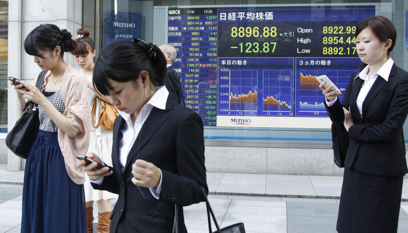 Women operate mobile phones in front of the stock index display of a securities firm in Tokyo Monday, July 9, 2012. Asian stocks were lower Monday after a disappointing U.S. jobs report stoked concern that the world's biggest economy remains mired in weak growth. (AP Photo/Koji Sasahara)