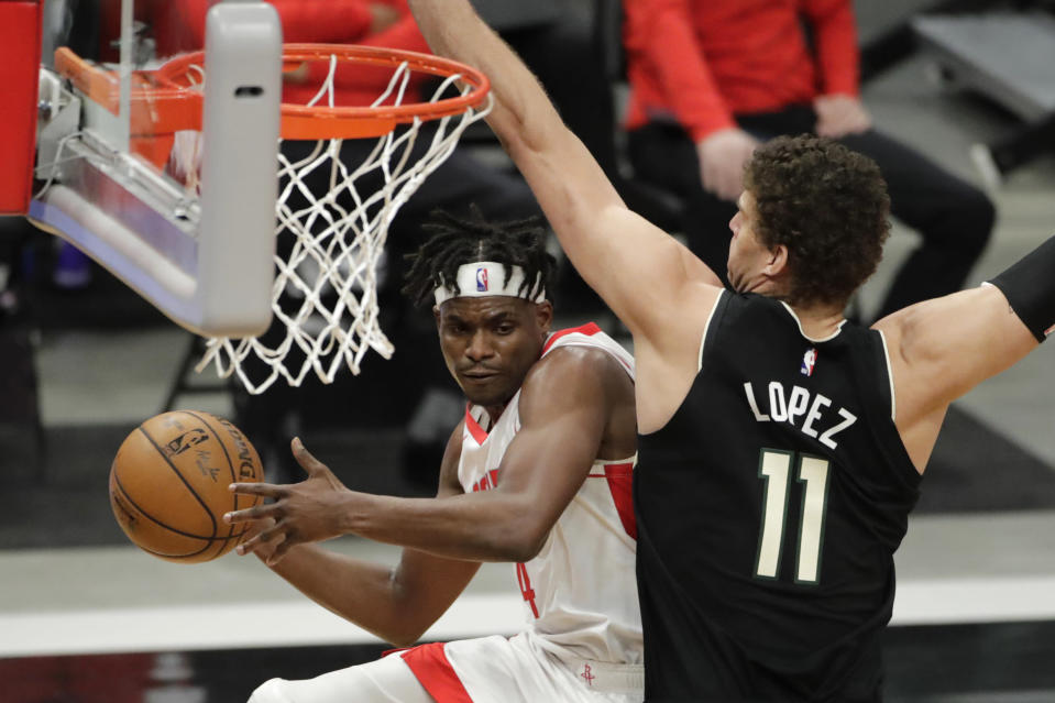 Houston Rockets' Danuel House Jr. (4) passes the ball around Milwaukee Bucks' Brook Lopez (11) during the first half of an NBA basketball game Friday, May 7, 2021, in Milwaukee. (AP Photo/Aaron Gash)