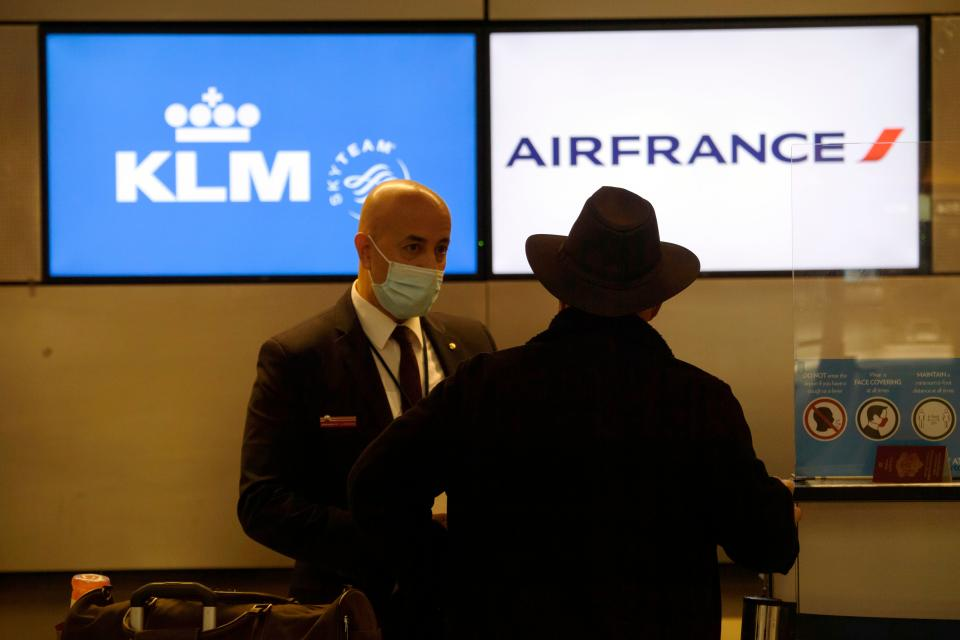 An employee wears a face mask as a passenger checks-in for a flight at the Air France and KLM counter inside the Tom Bradley International Terminal (TBIT) at Los Angeles International Airport (LAX) amid increased Covid-19 travel restrictions on January 25, 2021 in Los Angeles, California. - President Joe Biden will re-impose a Covid-19 travel ban on most non-US citizens who have been in Britain, Brazil, Ireland and much of Europe, a White House official said, as the new administration ramps up its pandemic response. (Photo by Patrick T. FALLON / AFP) (Photo by PATRICK T. FALLON/AFP via Getty Images)