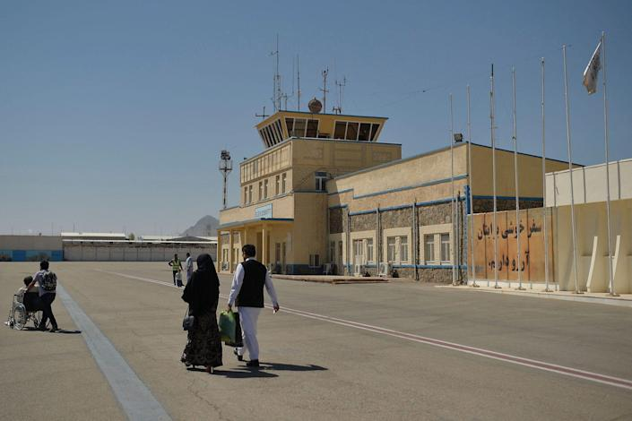 passengers on tarmac at kabul airport in afghanistan