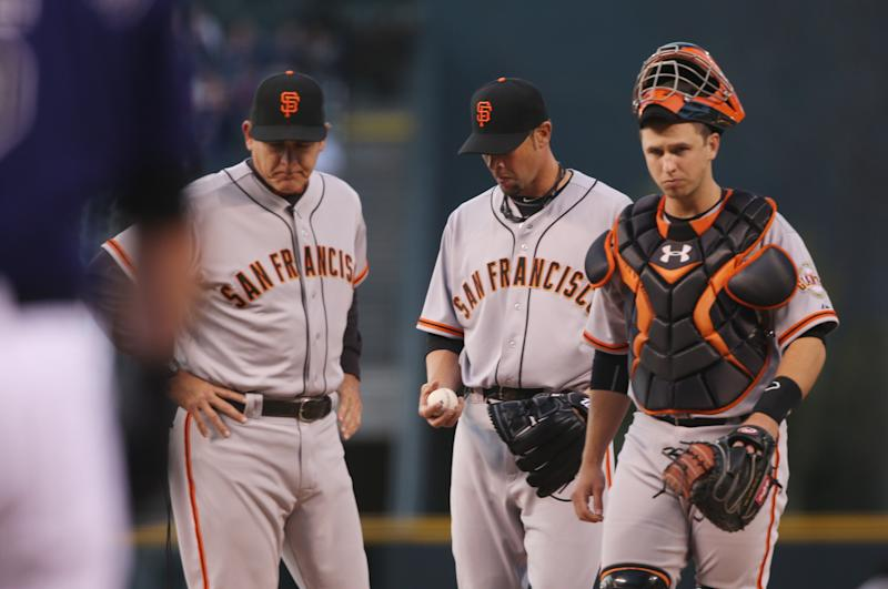 From left, San Francisco Giants pitching coach Dave Righetti confers with starting pitcher Ryan Vogelsong and catcher Buster Posey after Vogelsong gave up a three-run home run to Colorado Rockies' Wilin Rosario in the first inning of a baseball game in Denver on Monday, April 21, 2014. Vogelsong gave up a solo home run to the Rockies' Nolan Arenado as well in the inning. (AP Photo/David Zalubowski)