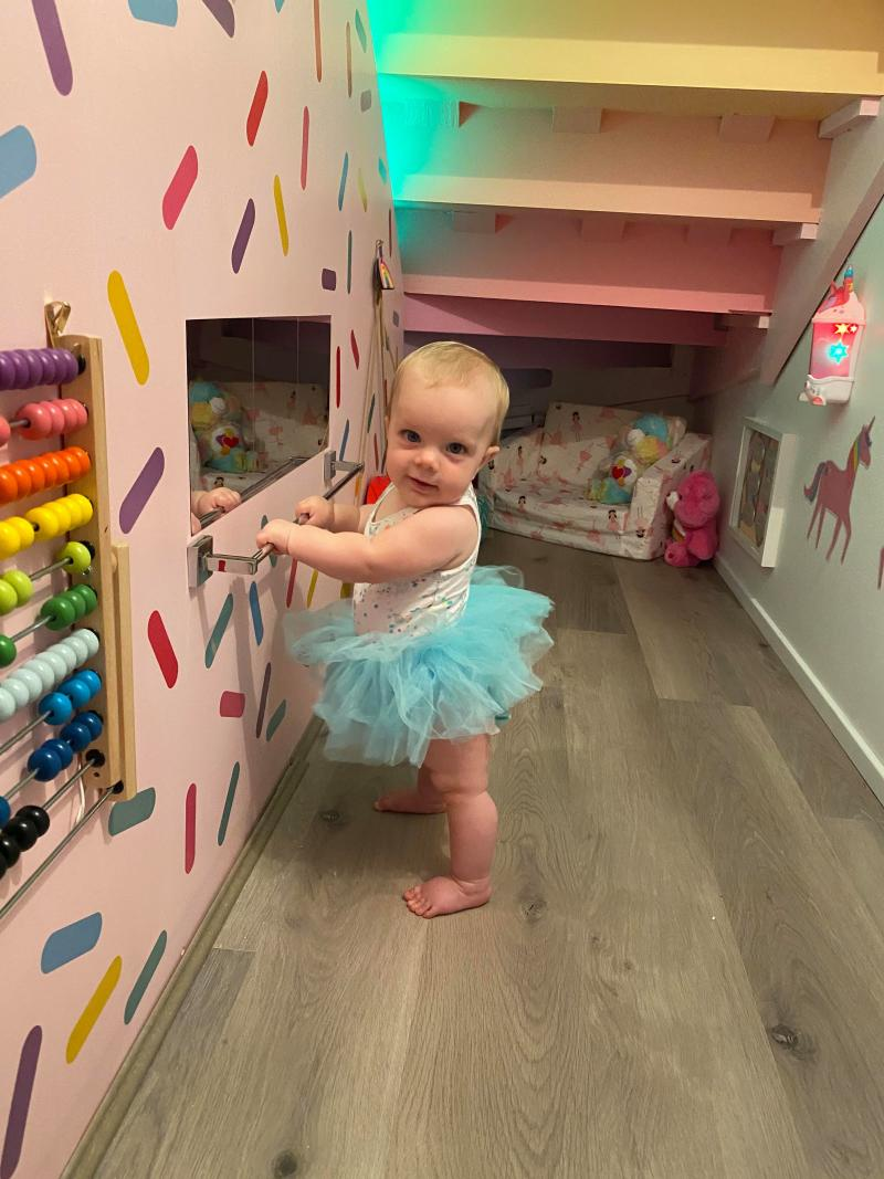 baby girl in tutu poses in under stair colourful rainbow playroom